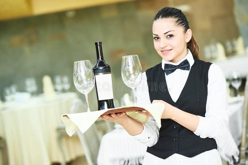 拿着瓶酒和玻璃的女服务员 免版税库存照片