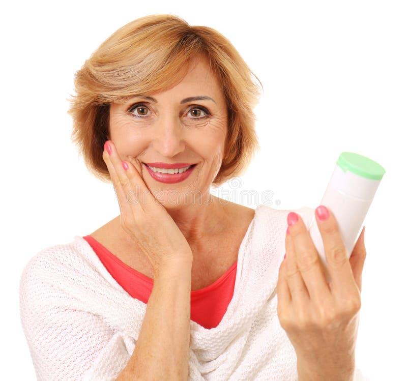 拿着瓶防皱化妆水的资深妇女画象 免版税库存照片