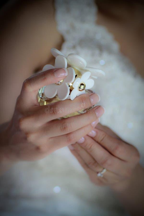 拿着瓶雏菊香水的新娘手 免版税库存图片