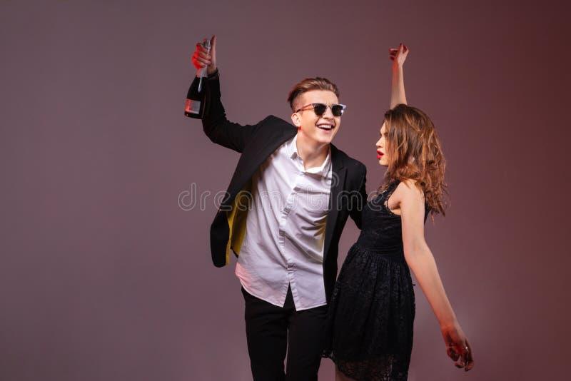 拿着瓶香槟和跳舞的愉快的夫妇 免版税图库摄影