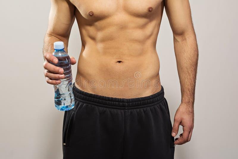 拿着瓶水的人特写镜头 免版税图库摄影
