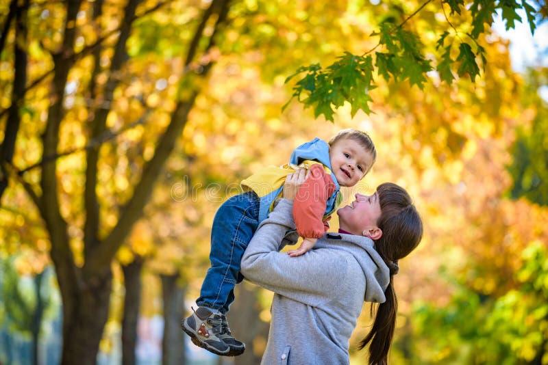拿着甜小孩男孩,家庭的愉快的年轻母亲获得乐趣 库存照片