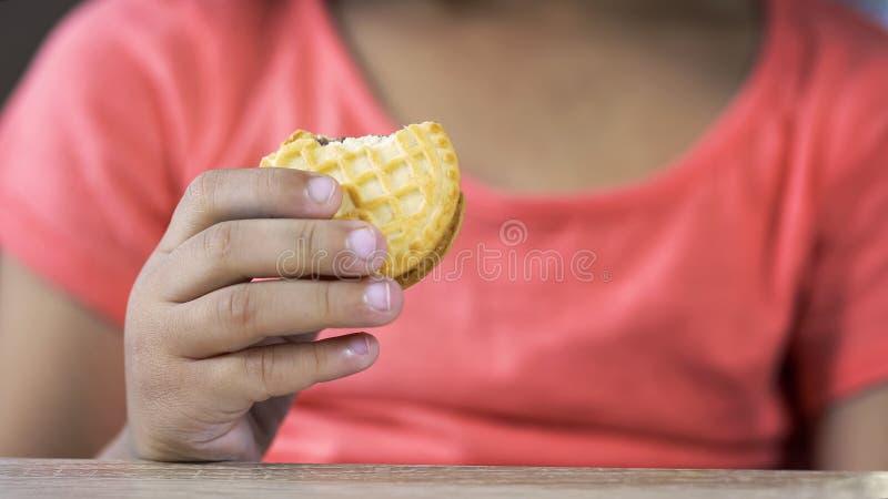 拿着甜曲奇饼,不健康的营养,特写镜头的逗人喜爱的学龄前女孩 库存图片