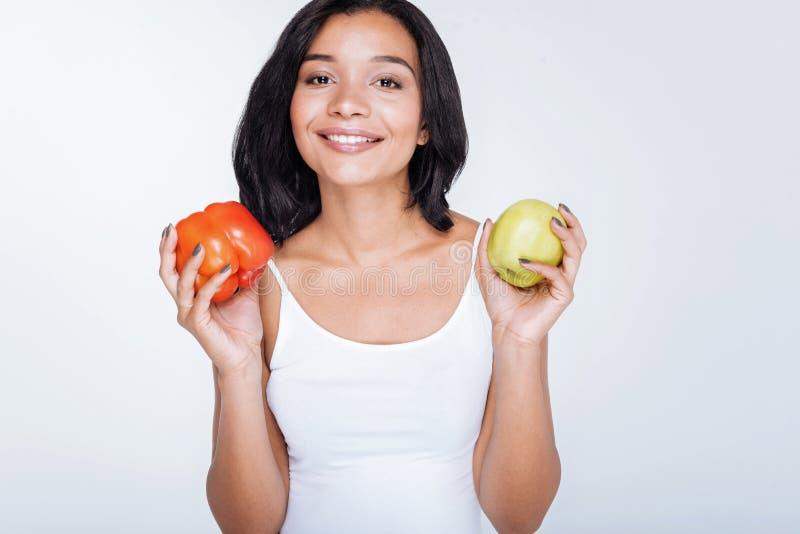 拿着甜椒和苹果的快乐的少妇 库存照片