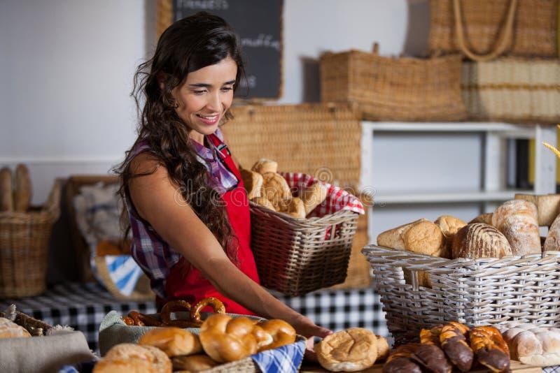 拿着甜食物的篮子在面包店部分的女职工 免版税库存照片