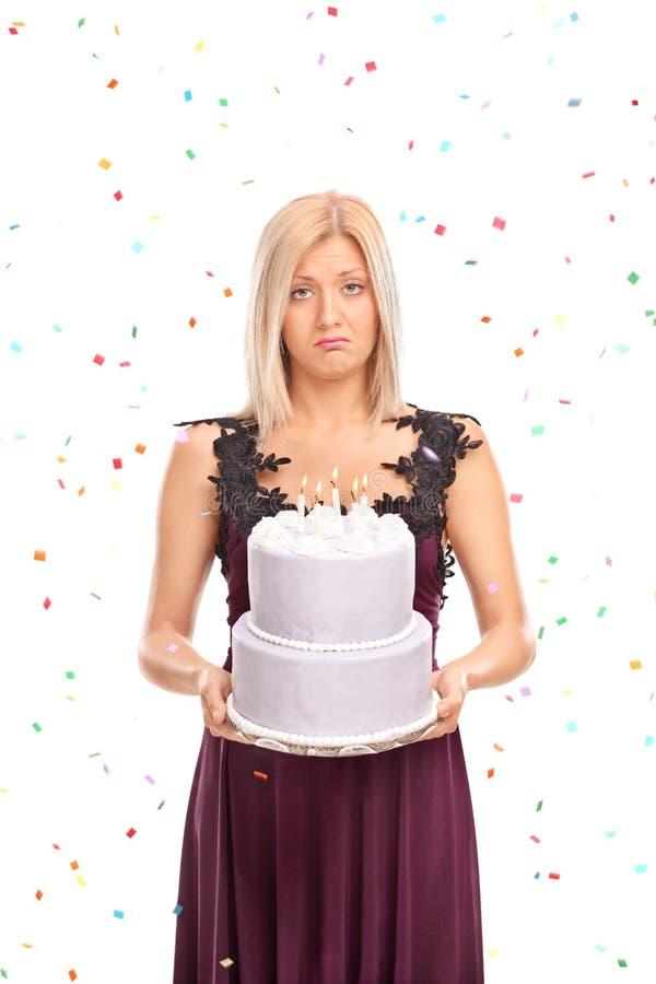 拿着生日蛋糕的哀伤的少妇 免版税库存照片