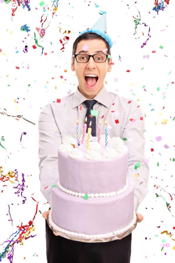 拿着生日蛋糕的年轻快乐的人 免版税库存照片