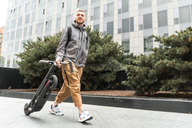 拿着电反撞力滑行车的年轻可爱的微笑的人,当散步在街道时 免版税库存图片