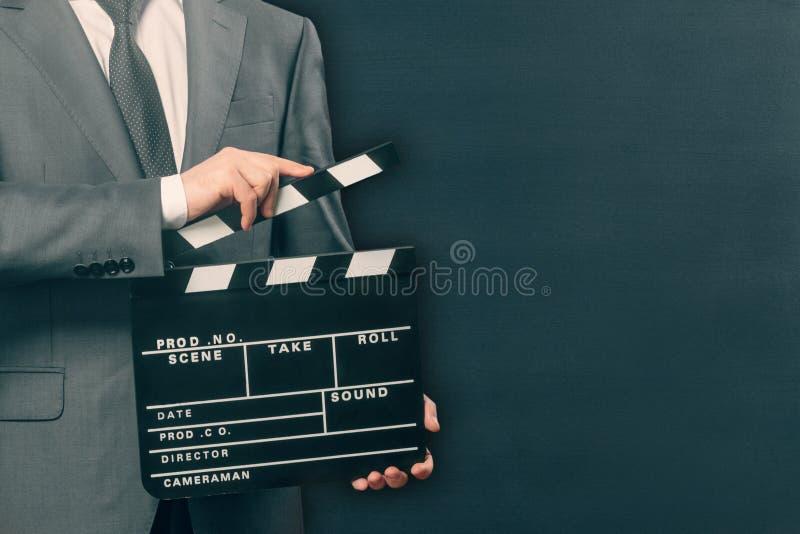 拿着电影在黑色的人拍板 免版税库存图片