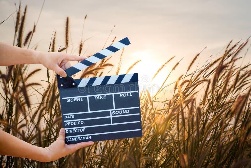 拿着电影拍板的人手被隔绝在自然背景 免版税库存图片