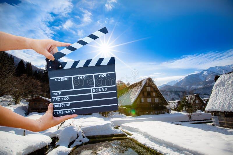 拿着电影拍板的人手被隔绝在自然背景 免版税库存照片