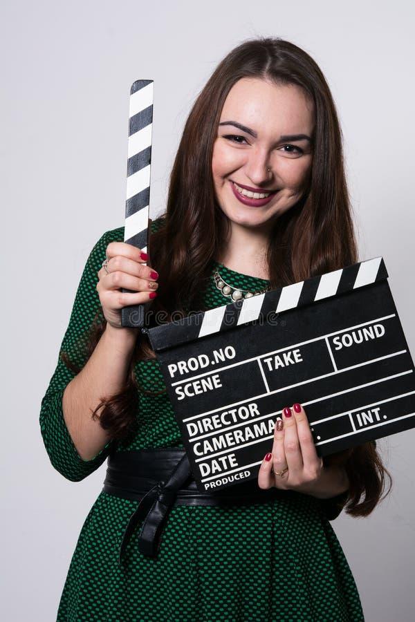 拿着电影拍板的少妇 免版税库存图片