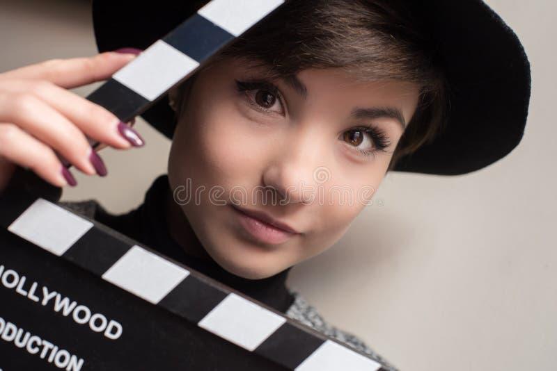 拿着电影拍板的年轻女演员画象 图库摄影