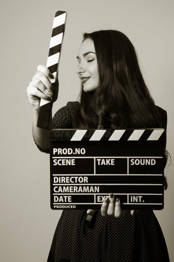 拿着电影拍板的画象妇女 免版税库存图片