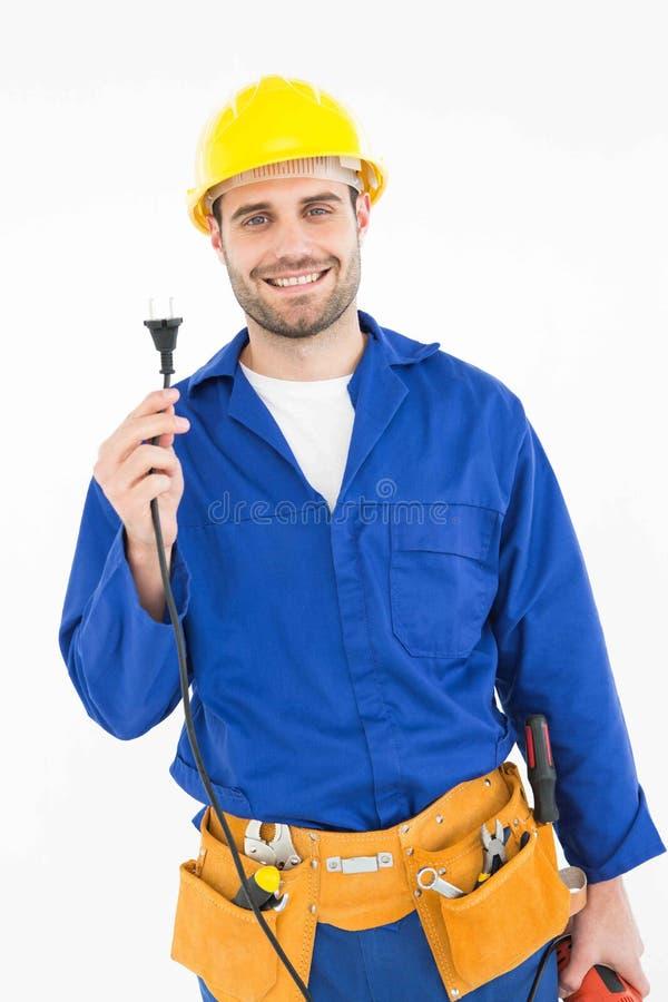 拿着电火花塞的微笑的安装工 免版税库存图片