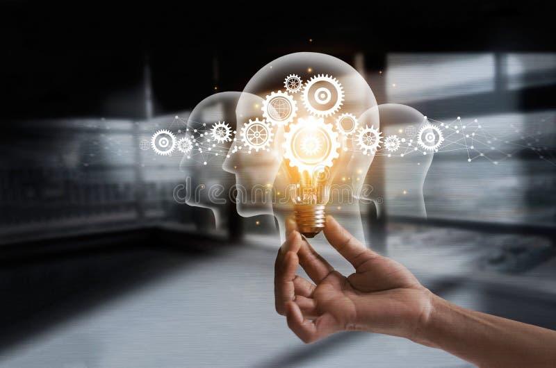 拿着电灯泡和嵌齿轮的手里面 想法和想象力 库存照片