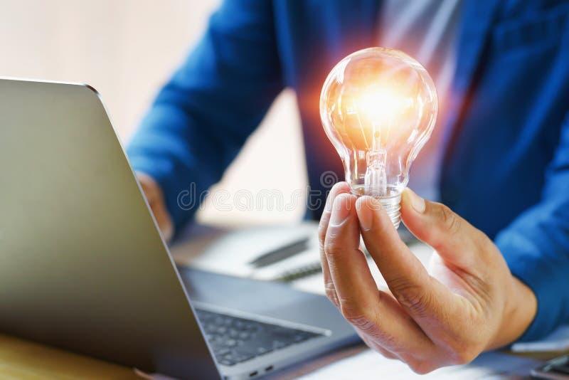 拿着电灯泡的商人在办公室 savin的创造性的想法 免版税库存图片