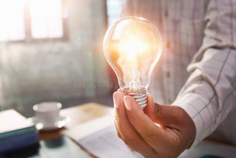拿着电灯泡的商人手在办公室 概念救球能量力量 库存照片