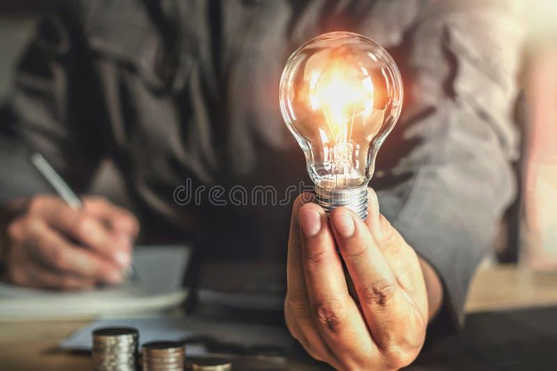 拿着电灯泡的商人手 与创新的想法概念 免版税库存照片