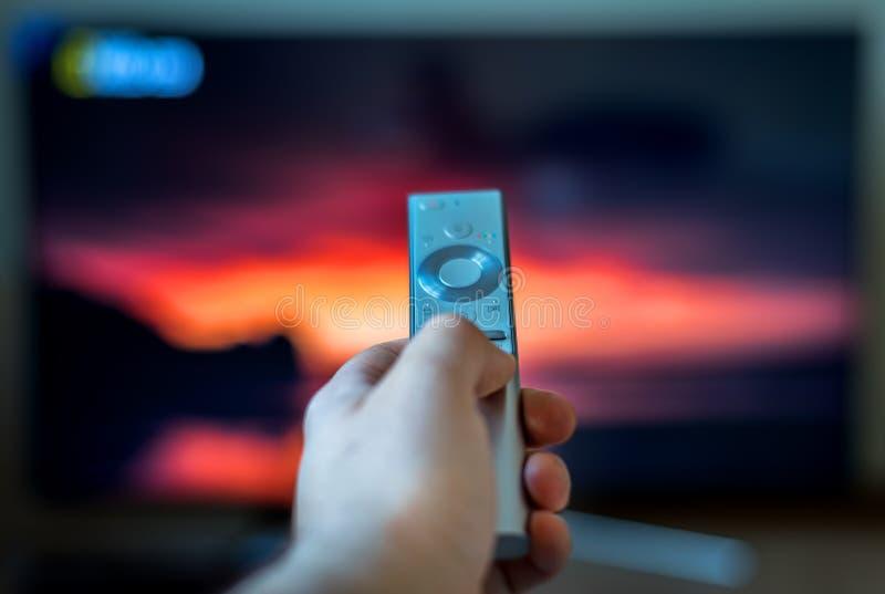 拿着电视的男性手遥控 免版税库存照片