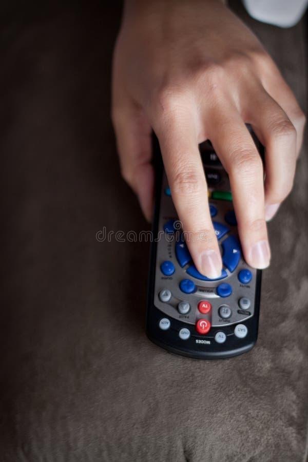 拿着电视遥控Upclose的左手 免版税库存照片