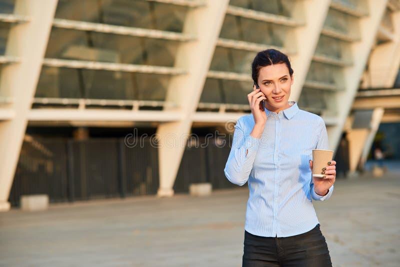 拿着电话和杯子的女实业家 免版税图库摄影