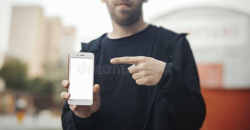 拿着电话在右手和显示在机动性屏幕上的有胡子的人  免版税库存照片