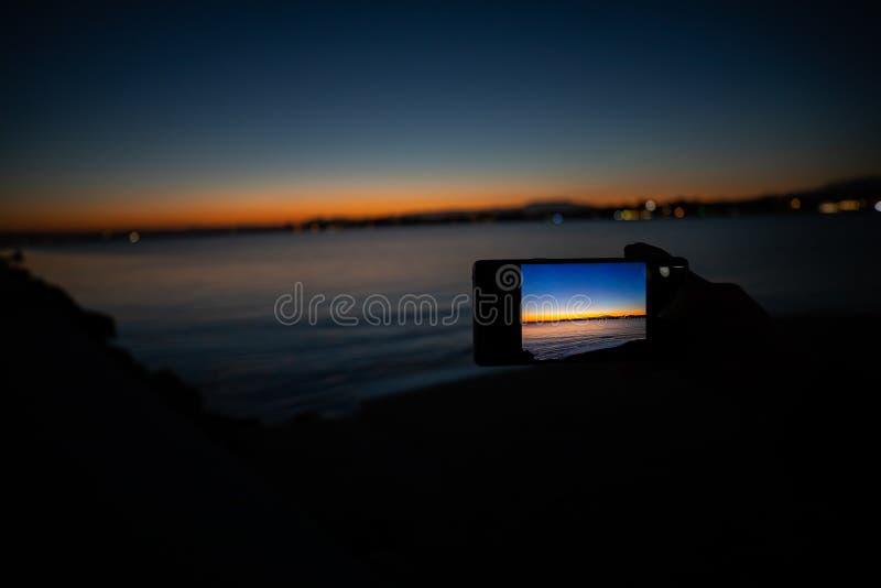 拿着电话的人的手拍日落的照片 图库摄影
