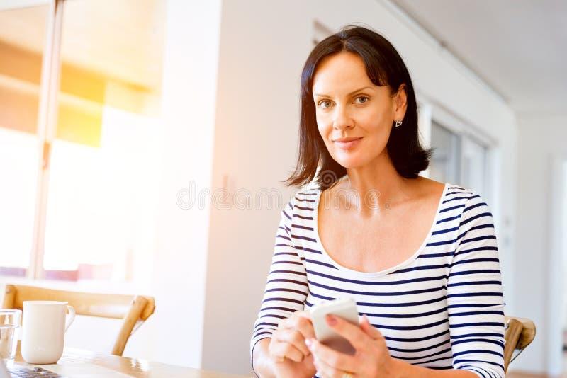 拿着电话的可爱的妇女画象 库存图片