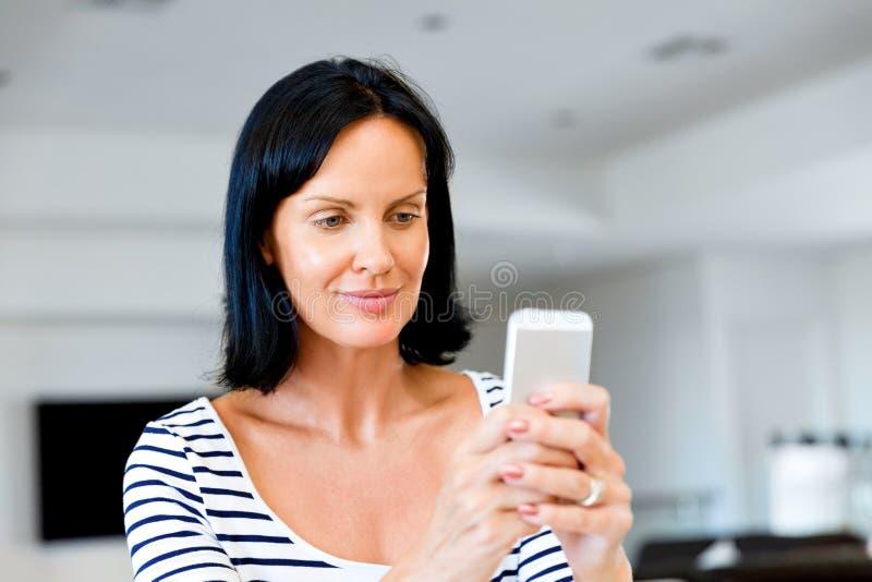 拿着电话的可爱的妇女画象 图库摄影