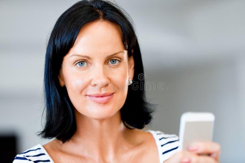 拿着电话的可爱的妇女画象 免版税库存图片