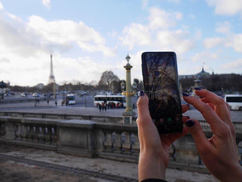 拿着电话的妇女手和拍埃菲尔铁塔的照片 在都市空间 免版税图库摄影
