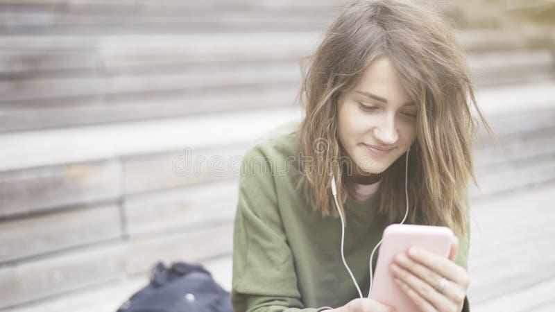 拿着电话的年轻人微笑的俏丽的女孩的特写镜头听到音乐 免版税图库摄影