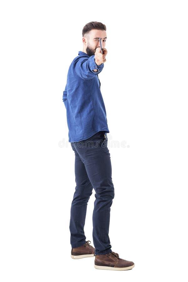 拿着电话的年轻有胡子的商人作为假装的武器瞄准和射击在照相机 免版税库存图片