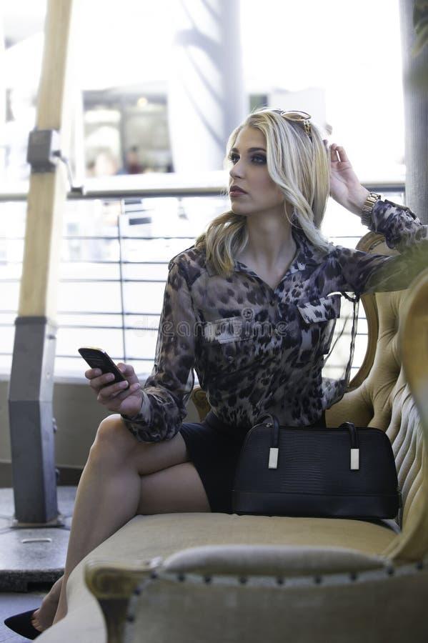 拿着电话的性感的白肤金发的都市妇女 库存照片