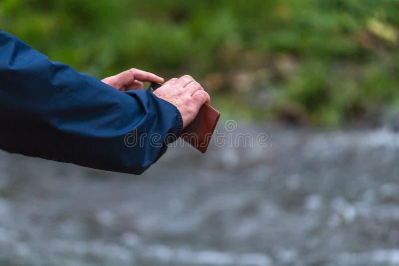 拿着电话的老人手 有智能手机扭角羚的老人 免版税库存图片