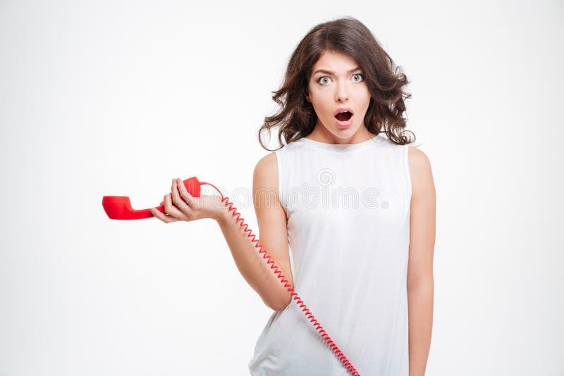 拿着电话管的震惊妇女 库存照片
