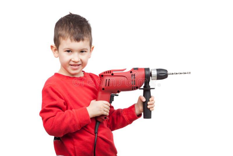 拿着电钻的愉快的小男孩画象  一点建筑工人 查出在白色 免版税图库摄影