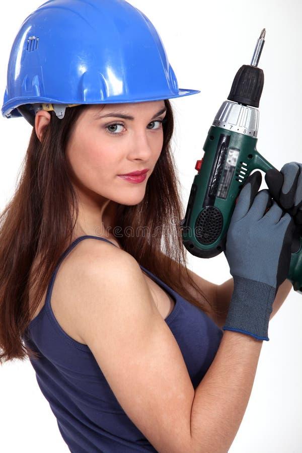 拿着电钻的女工匠 免版税库存图片