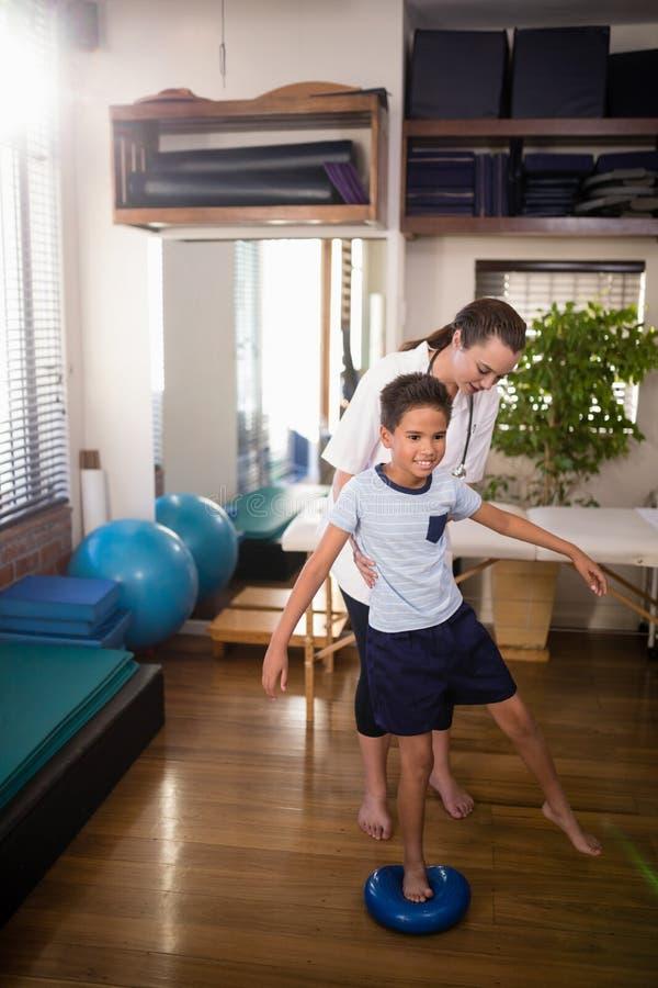 拿着男孩的女性治疗师站立在蓝色重音球 库存图片