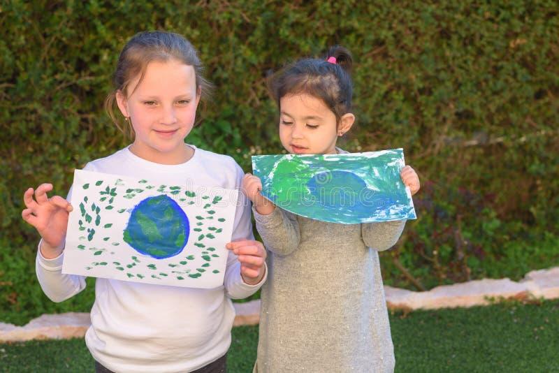 拿着画的地球地球的两逗人喜爱的女孩的画象 孩子获得的地球的paintig图片室外的乐趣 库存图片