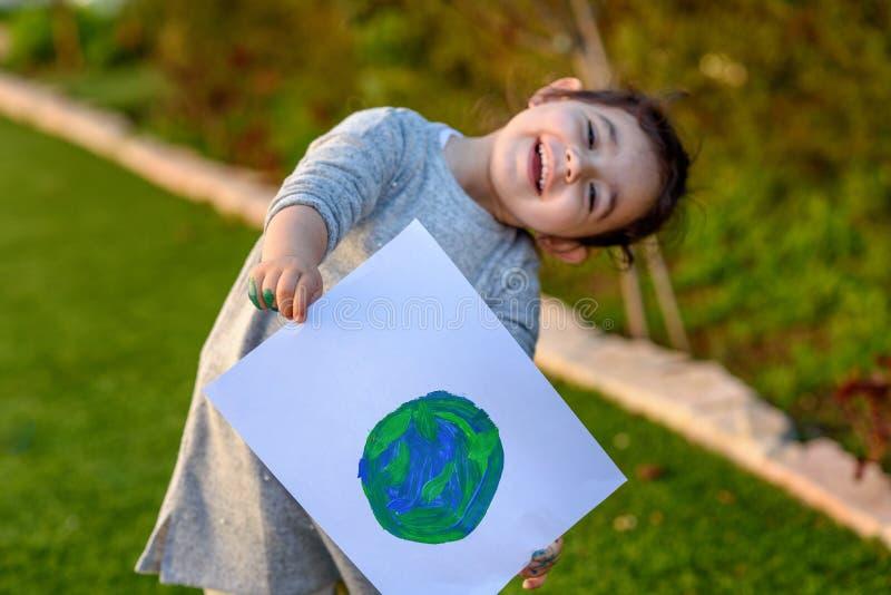 拿着画的地球地球的逗人喜爱的女孩的画象 儿童drawng地球的图片 免版税库存图片