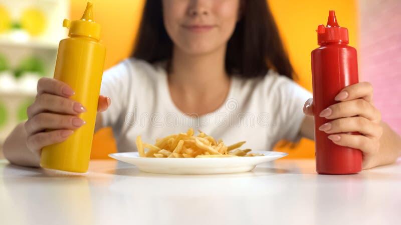 拿着番茄酱和芥末在薯条板材,不健康的膳食的深色的妇女 免版税图库摄影
