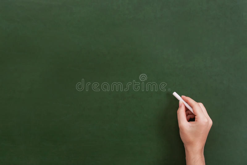 拿着白垩棍子的老师或学生手 库存图片