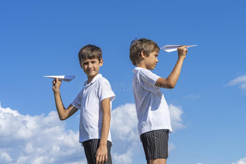 拿着白皮书飞机的两个男孩反对天空蔚蓝 免版税图库摄影