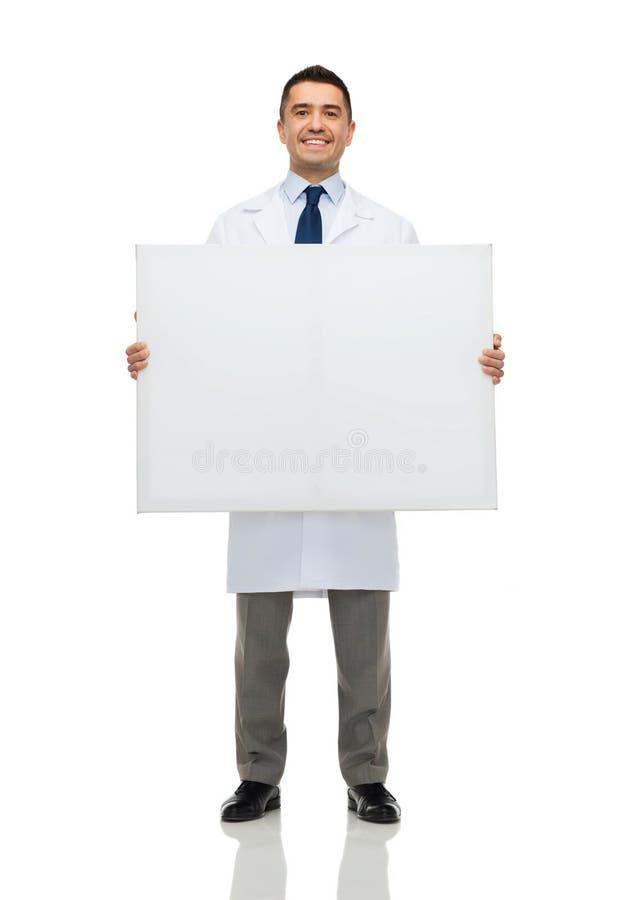 拿着白空白的委员会的微笑的男性医生 免版税库存图片