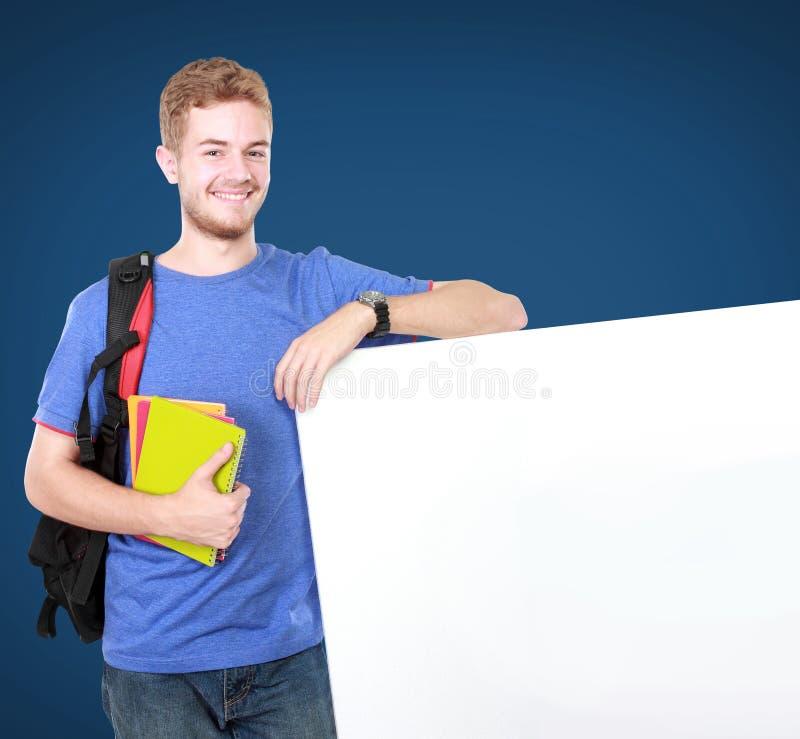 拿着白空白的委员会的年轻男学生 免版税库存照片