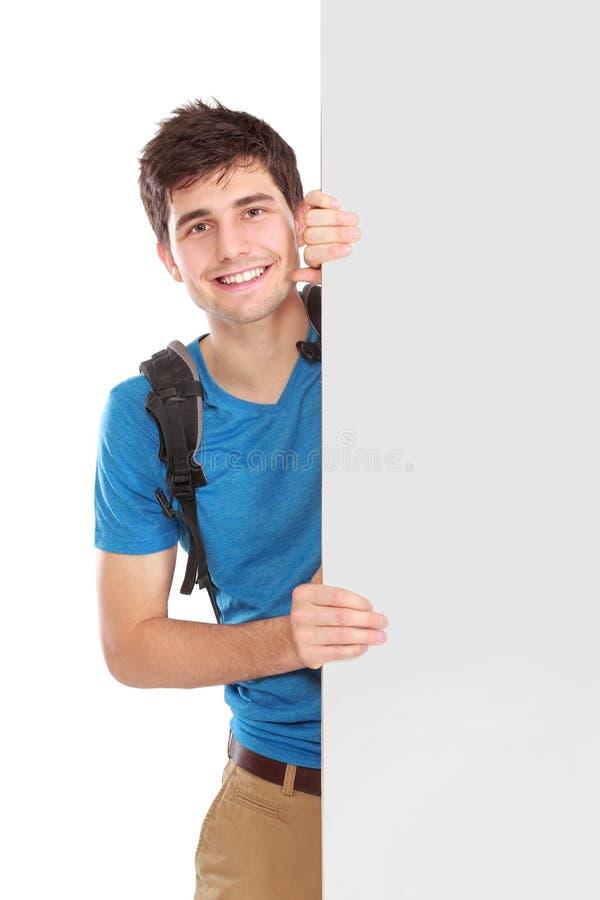 拿着白空白的委员会的年轻男学生 免版税库存图片