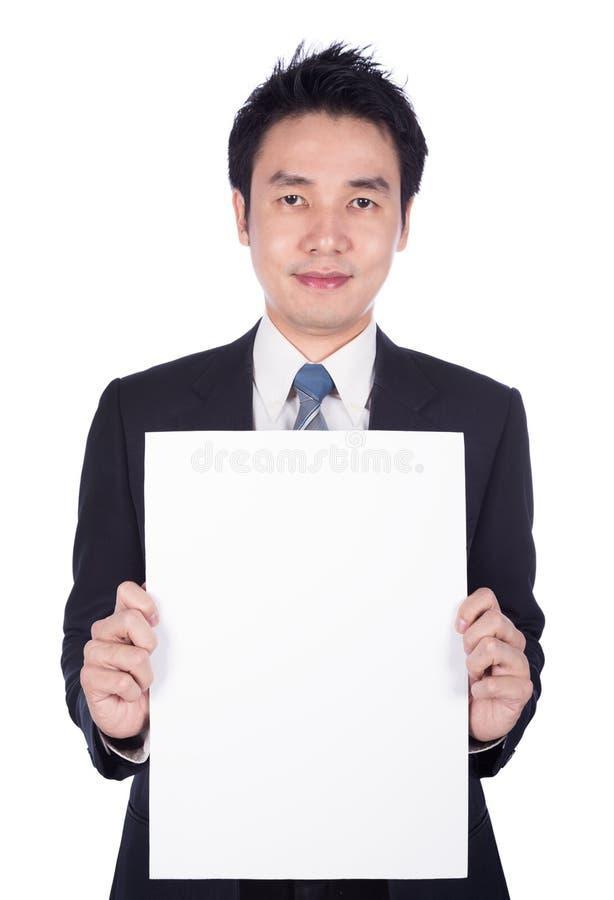 拿着白纸板料的商人被隔绝在白色 免版税图库摄影