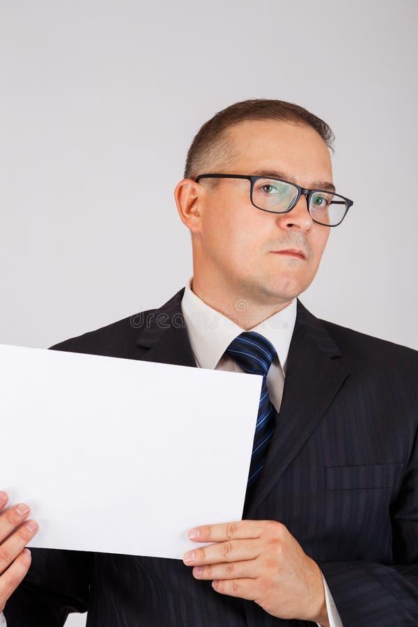 拿着白纸板料的商人 免版税库存照片